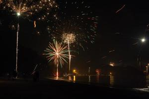 vackra fyrverkerier firar nytt år på stranden foto