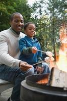 far och son som rostar marshmallows foto
