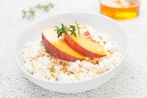 färsk hemlagad keso med honung, valnötter och persikor foto