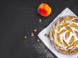 persika paj med sockerpulver över ett papper foto