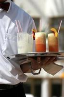 servitör med fruktcocktails foto