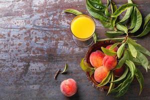 persikor på gren och juice foto