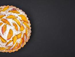 persika paj med sockerpulver på mörk med ett utrymme foto