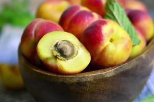 mogna röda aprikoser i en träskål. foto