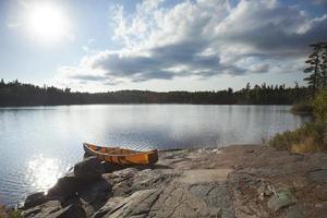 kanot på stenig strand av gränsvatten sjön nära solnedgången foto