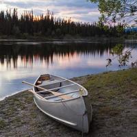 solnedgångshimmel och kanot på Teslin River Yukon Canada foto