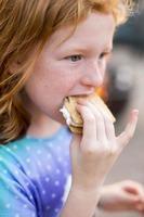 ung flicka äter en smore foto