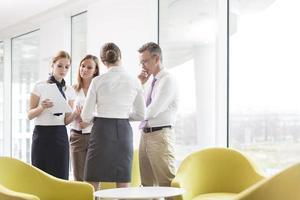 affärsmän diskuterar över dokument i kontorslobby foto