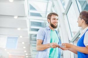 vacker ung flygvärdinna som kontrollerar dokument för manlig turist foto