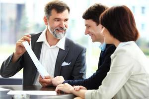 affärspartners som diskuterar dokument och idéer vid mötet foto