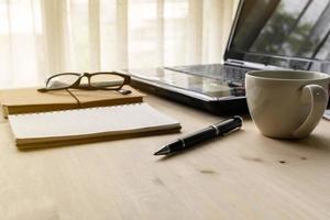 kopp kaffe med bärbar dator på träskrivbord och dokument foto