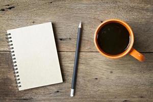 kaffe och anteckningsbok på träbakgrund foto