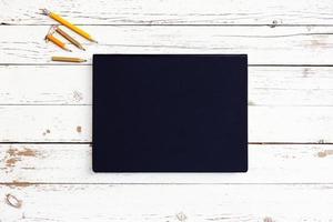 vitt tomt träbord med svart anteckningsbok foto