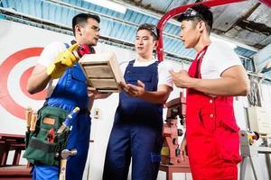 team av asiatiska arbetare som diskuterar produkt foto
