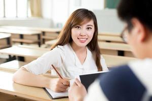 två asiatiska studenter diskuterar innehåll på surfplattan foto
