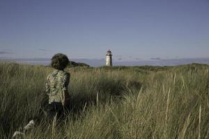 tjej med spaniel går genom sanddyner till ett ljushus foto