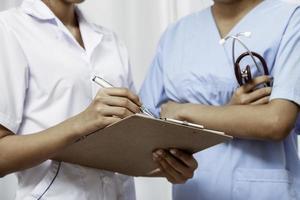 sjuksköterskor diskuterar patientens journal foto