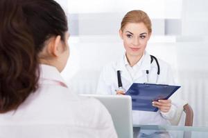 kvinnlig läkare som pratar med patienten foto
