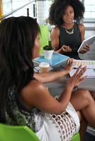två kollegor som diskuterar idéer med hjälp av en surfplatta foto