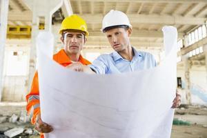 manliga arkitekter diskuterar över planen på byggarbetsplatsen foto