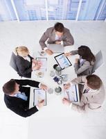 affärsmän som diskuterar på grafer vid konferensbordet foto