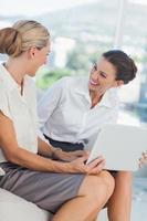 affärskvinnor skrattar medan de arbetar tillsammans foto