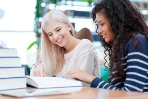 två leende kvinna läser bok tillsammans foto