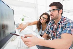 leende kollegor som pekar datorn tillsammans foto
