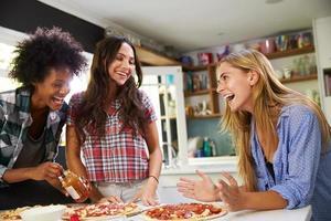 tre kvinnliga vänner som gör pizza i köket tillsammans