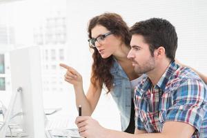 glada kollegor som arbetar tillsammans med datorn foto