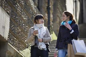 två glada kvinnor som shoppar tillsammans, har roligt och skrattar foto