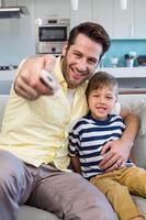 far och son tittar på tv tillsammans i soffan foto