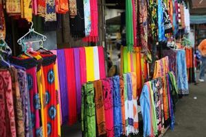 rader med färgglada silkesjalar som hänger på en marknad foto