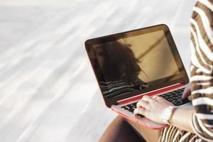 den unga kvinnan som använder den bärbara datorn foto