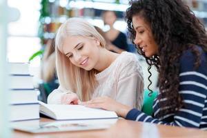 glada två flickor som läser bok tillsammans foto