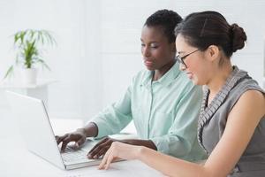 affärskvinnor som arbetar tillsammans vid skrivbordet foto