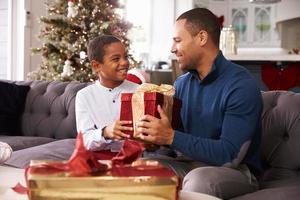 far och son öppnar julklappar hemma tillsammans foto