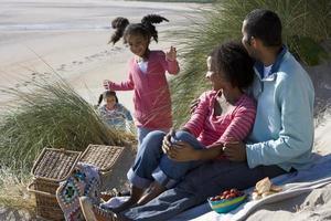 familj sitter på stranden