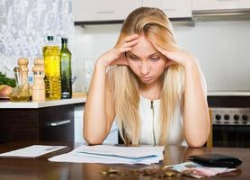 sorglig kvinna som beräknar familjens budget foto