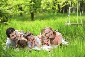 lycklig familj som har picknick i naturen foto