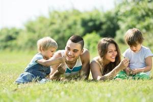familj på fyra i soliga park foto