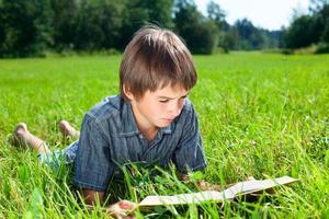 barn läser bok utomhus foto