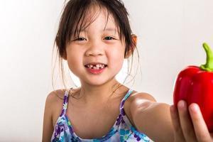 barn med paprika / barn som håller paprika bakgrund foto