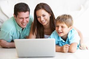 unga föräldrar, med barn, på bärbar dator foto