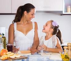 kvinna och barn matlagning strudel foto