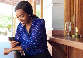 leende affärskvinna som läser textmeddelande på mobiltelefonen foto