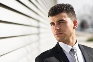 ung affärsman nära en kontorsbyggnad som bär svart kostym foto