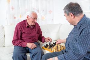 äldre män som spelar schack foto