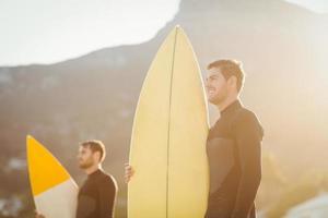 två män i våtdräkter med en surfbräda foto