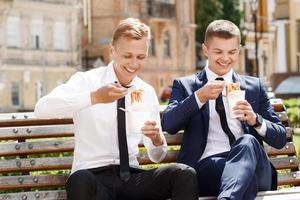 två stiliga män som äter kinesiska nudlar foto